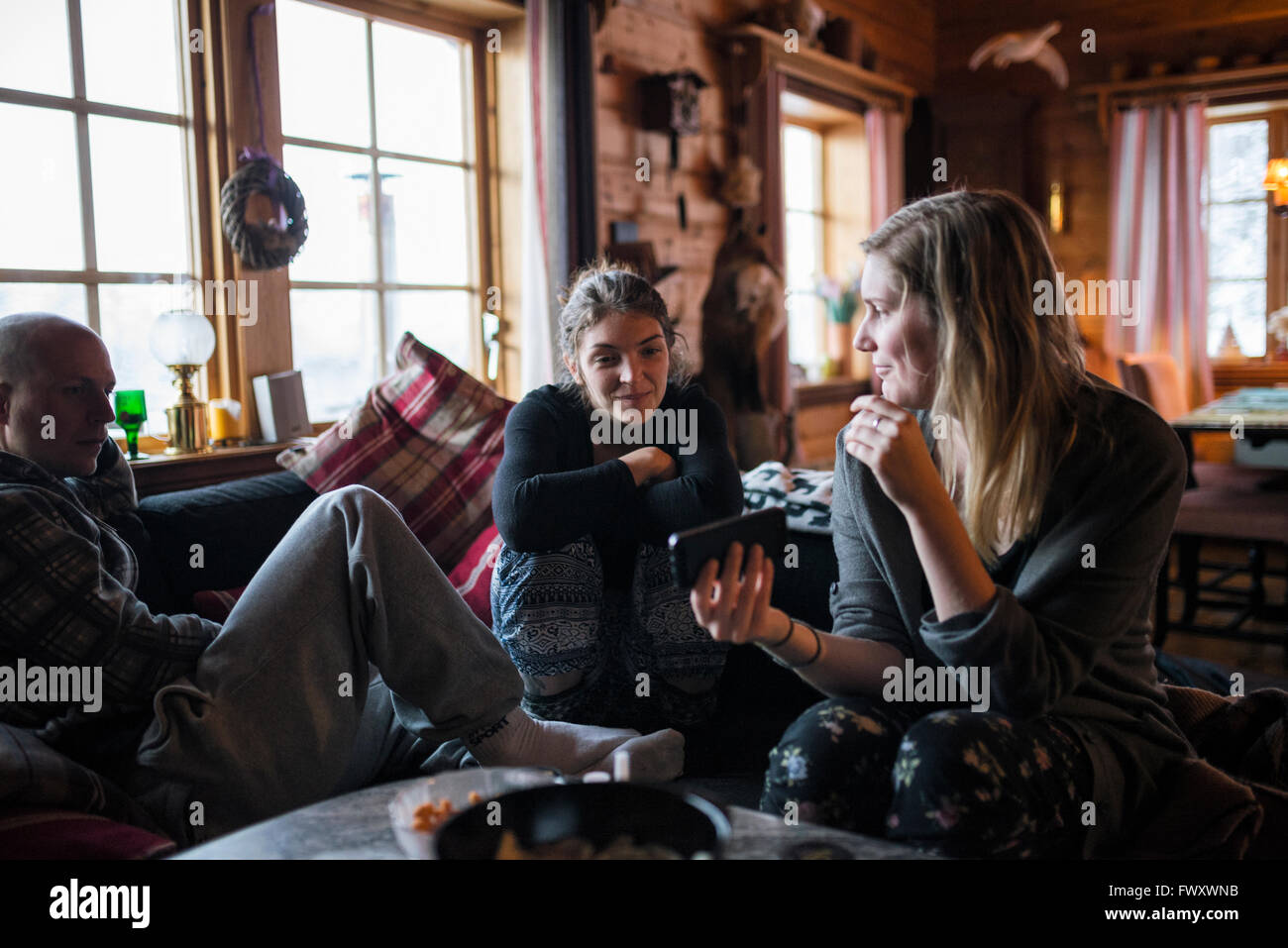 Sweden, Young woman showing smart phone to friends in log cabin Stock Photo