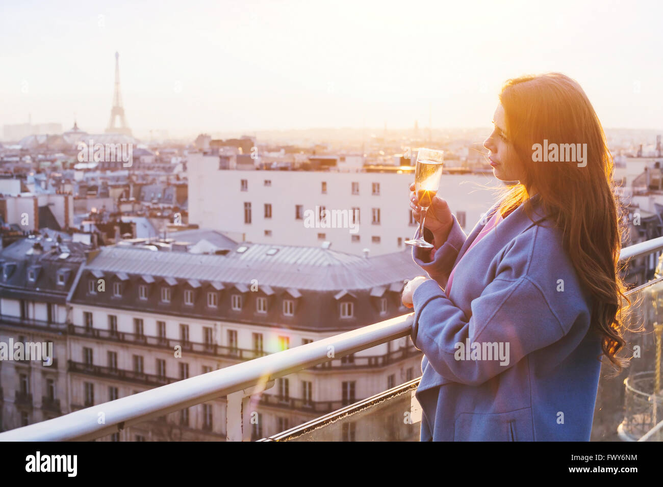 woman enjoying panoramic view of Paris and Eiffel tower at sunset, holding glass of wine or champagne in rooftop - Stock Image