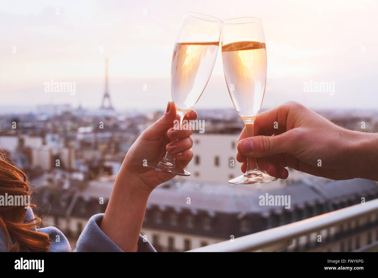 two glasses of champagne or wine, couple in Paris, romantic celebration of engagement or anniversary - Stock Image