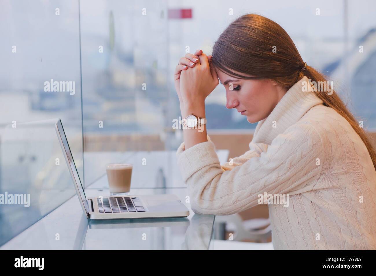 unemployment concept, problem, sad tired woman in front of laptop in modern bright cafe interior - Stock Image