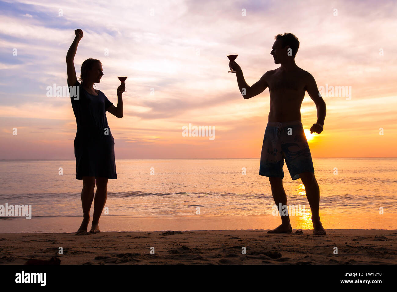 beach festival or party with friends, joyful happy people celebrating life, couple dancing with cocktails - Stock Image