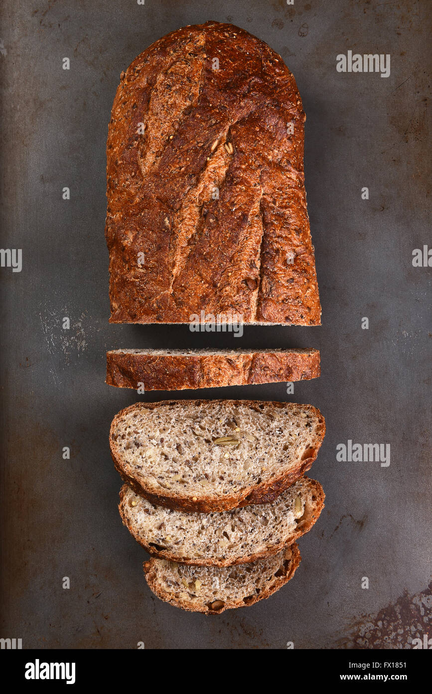 Top view of a loaf of multi-grain bread on a baking sheet. The loaf is partially sliced, Stock Photo
