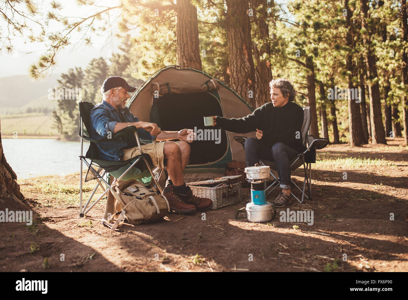 Portrait of senior couple camping by a lake, with woman giving a cup of coffee to man. - Stock Image