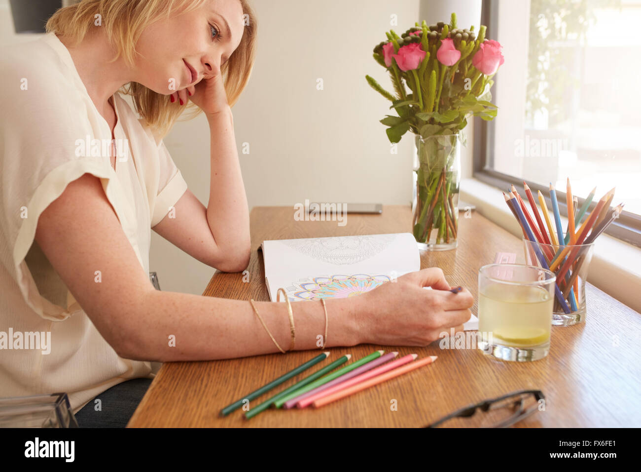 Woman drawing an adult coloring book while comfortably sitting at table by a window. - Stock Image