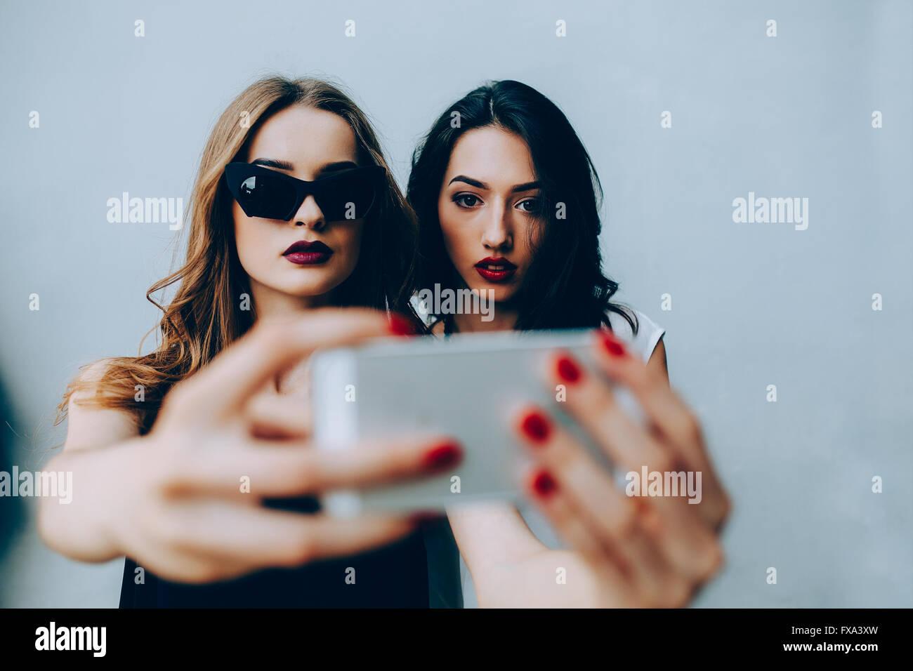 Two girlfriends taking a selfie - Stock Image