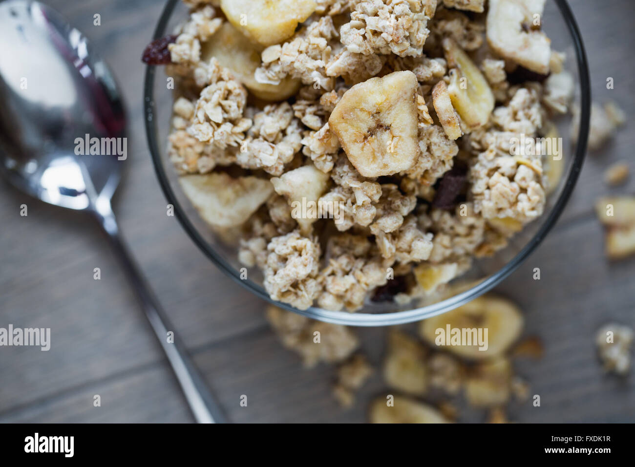 Bowl of granola with banana on wooden table. Stock Photo