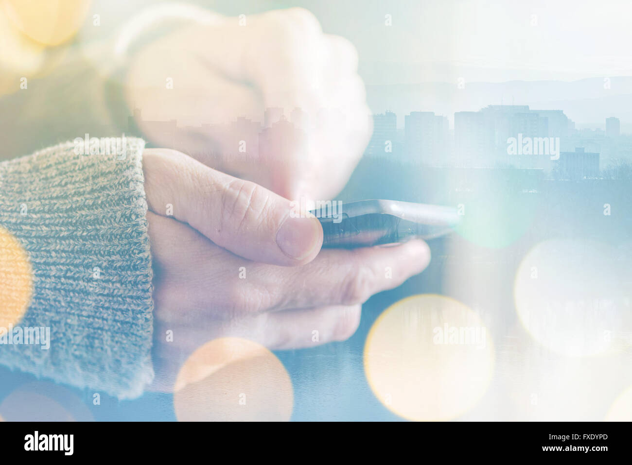 Man sending text message on smartphone, morning sunlight through the window, male hands using mobile phone device - Stock Image