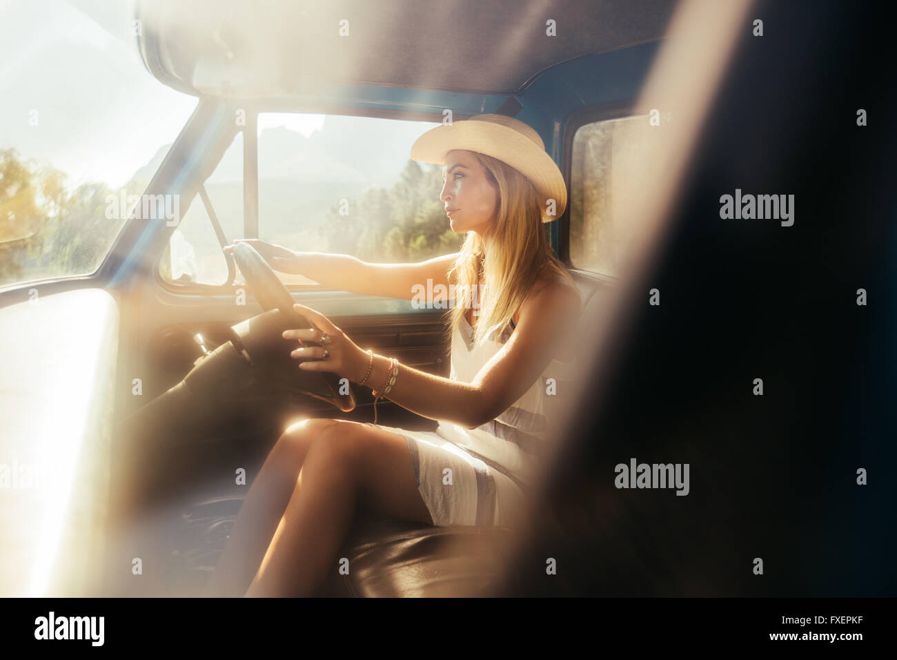 Portrait of beautiful young woman wearing a hat driving a car on sunny day. Young girl on a road trip. - Stock Image