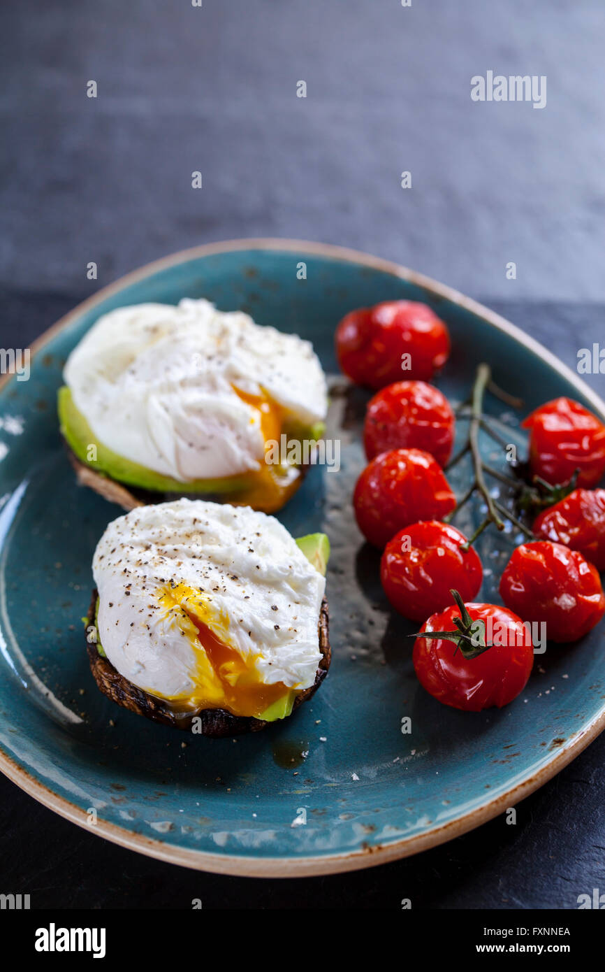 Breakfast, mushrooms with avocado and poached eggs and roast cherry tomatoes on the vine - Stock Image