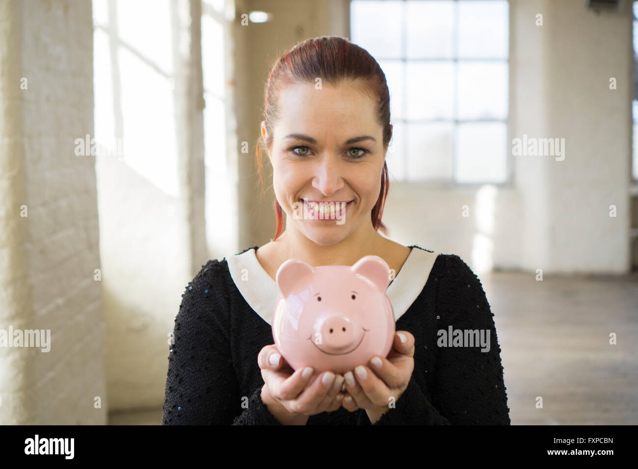 Happy woman holding a piggy bank smiling - Stock Image
