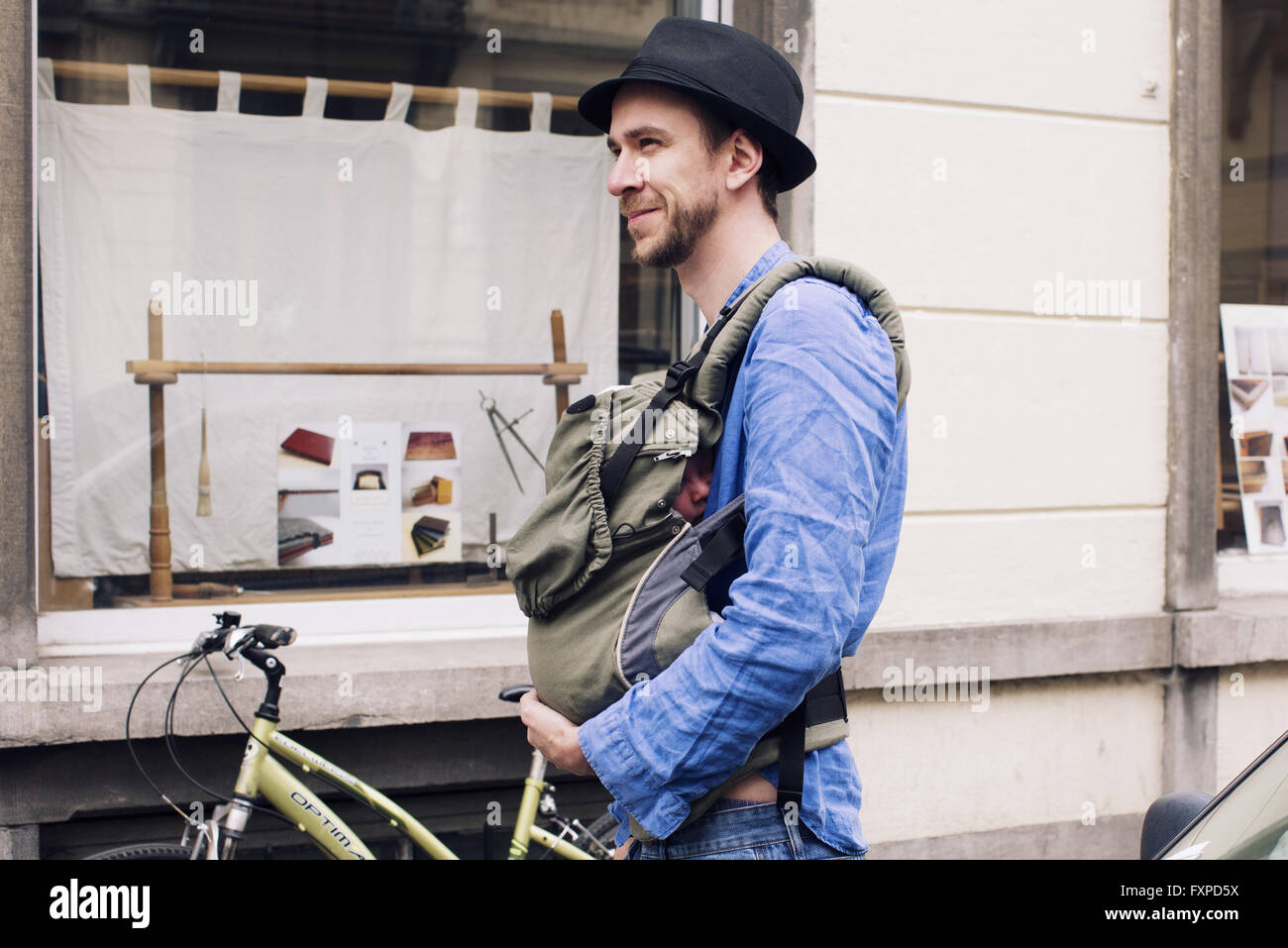Man out and about in the city with baby in carrier - Stock Image