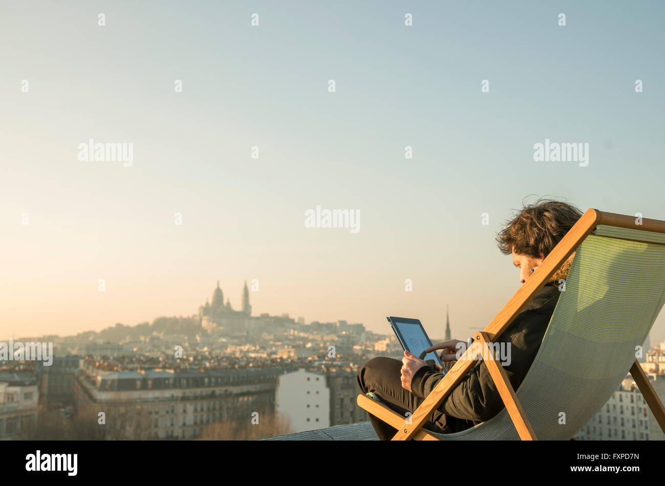 Man relaxing on rooftop terrace with digital tablet - Stock Image