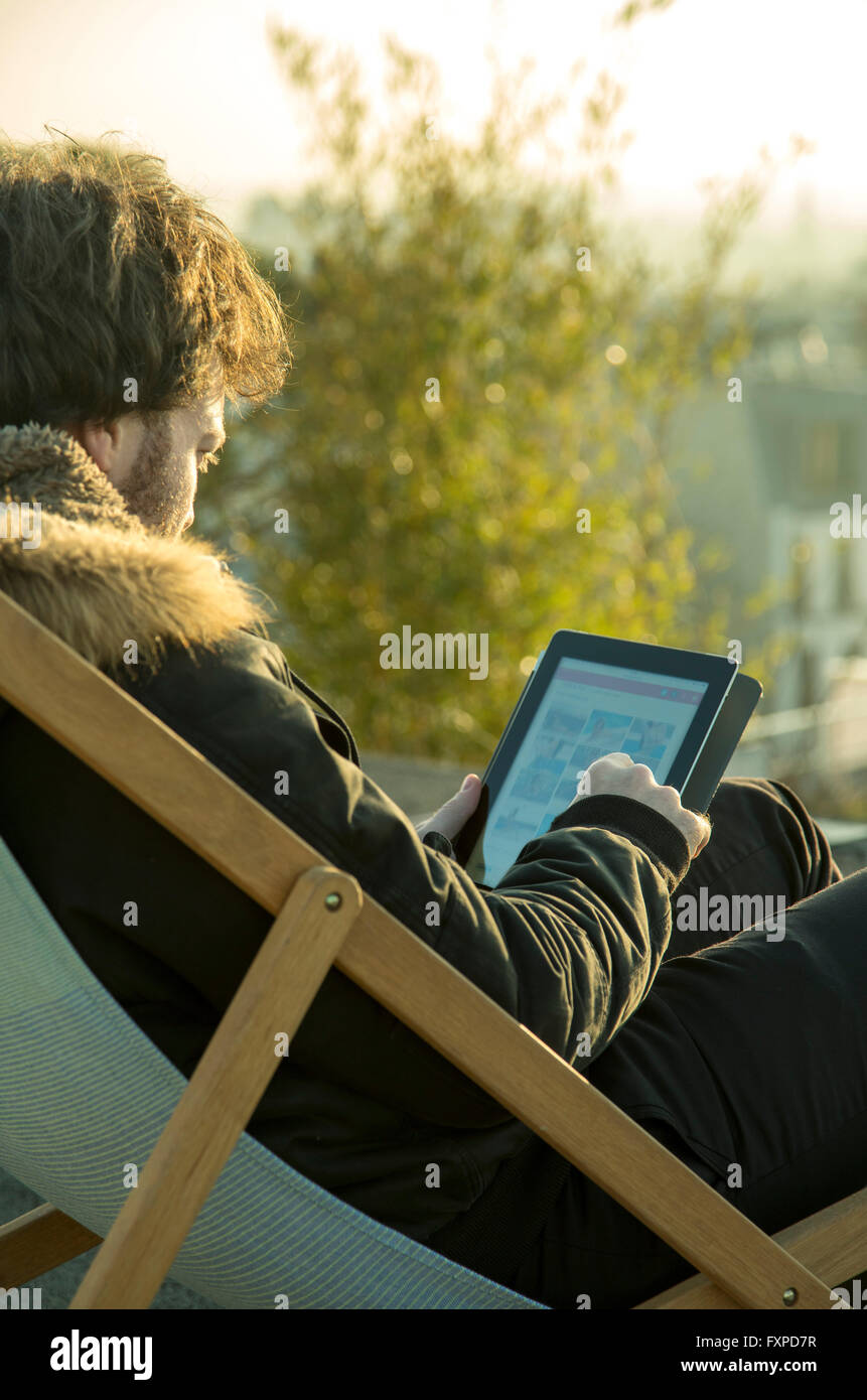 Man using digital tablet outdoors - Stock Image