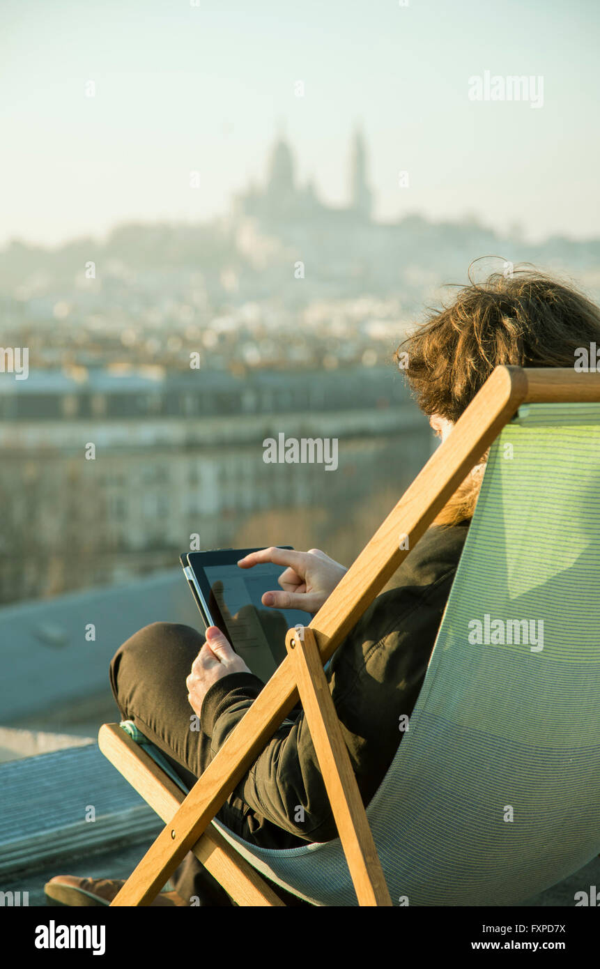 Man using digital tablet on rooftop terrace - Stock Image