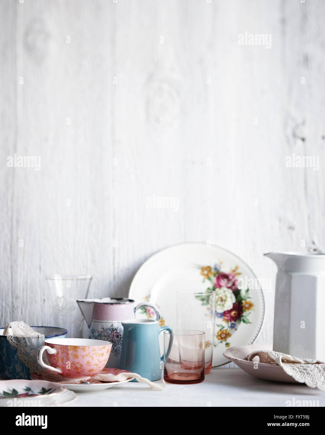 Variety of drinking glasses, plates and jugs on whitewashed table Stock Photo