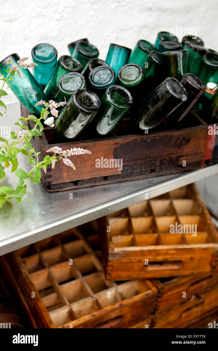 Wooden crate with upside down vintage bottles on terrace in rain Stock Photo