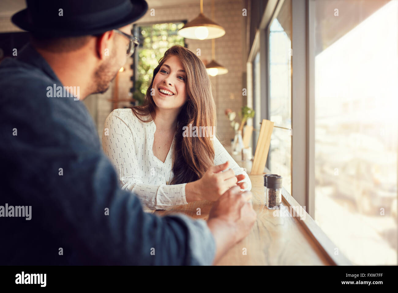 Smiling young woman sitting in a cafe and talking to her boyfriend. Young couple spending time at coffee shop. - Stock Image
