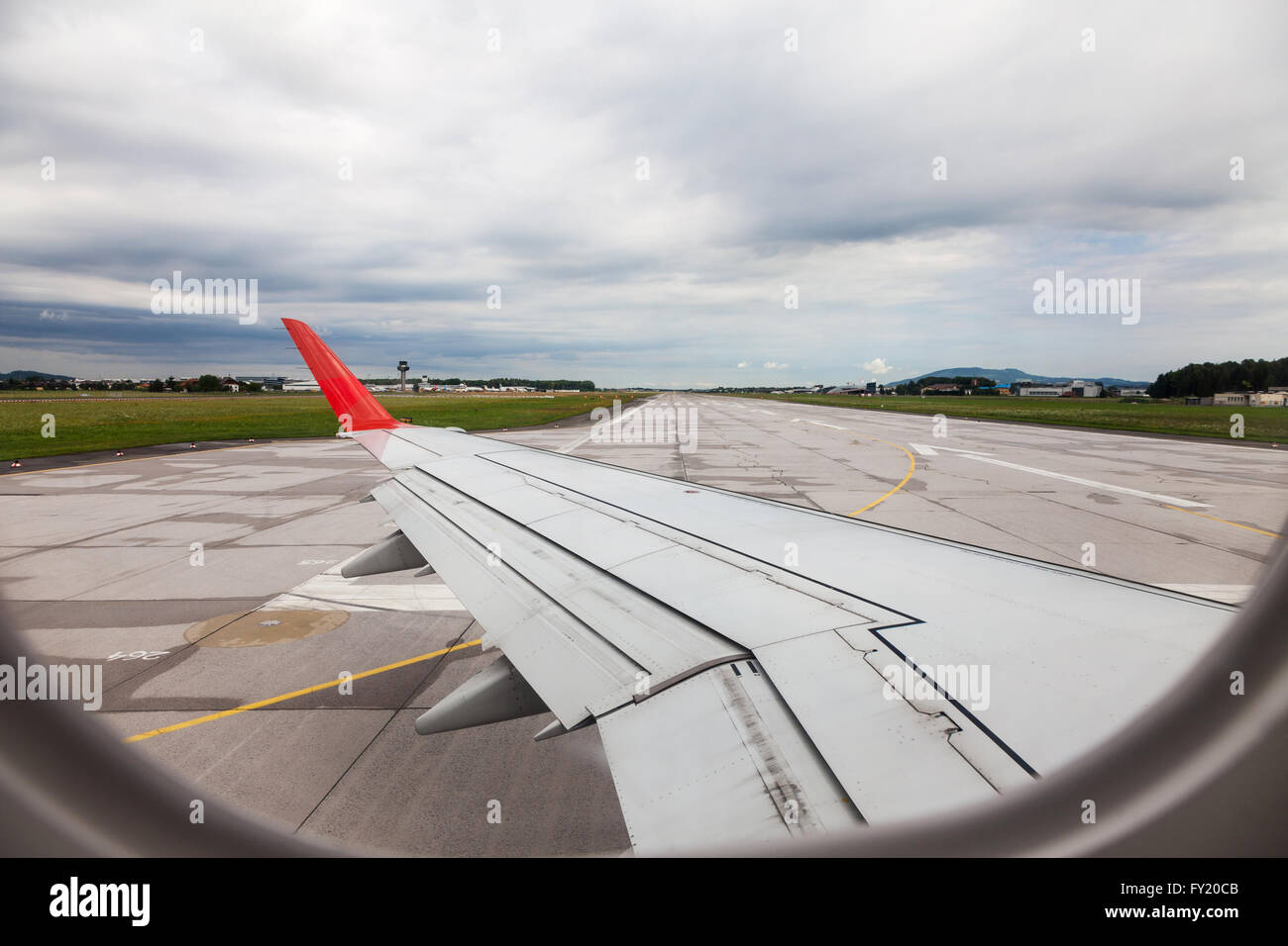 Looking through an airplane window at the runway taxiing on takeoff at Saltzburg airport Saltzburg Austria Europe - Stock Image