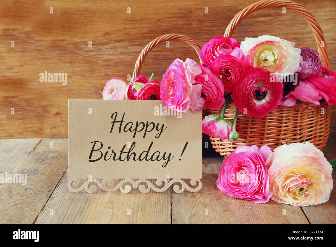 Pink flowers in the basket next to card with phrase happy birthday pink flowers in the basket next to card with phrase happy birthday on wooden table izmirmasajfo Image collections