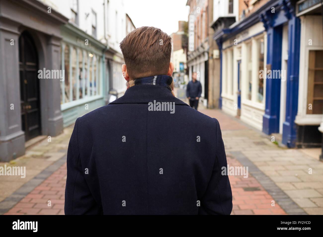 Rear View Of Young Man Walking Down Urban Street - Stock Image