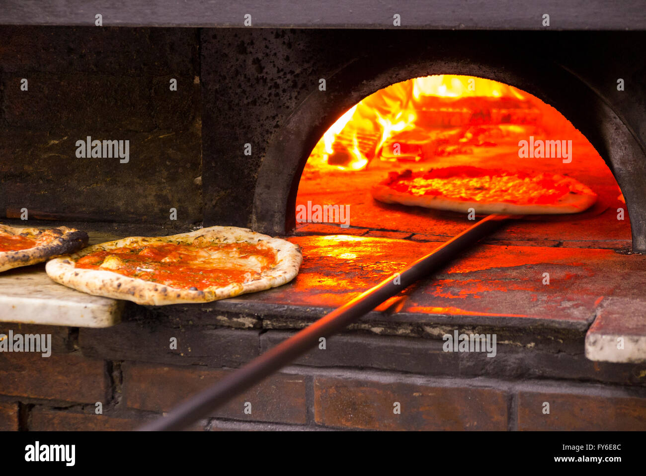Looking inside a wood burning pizza oven at pizzas being baked in famous Italian restaurant in Naples, Pizzeria - Stock Image