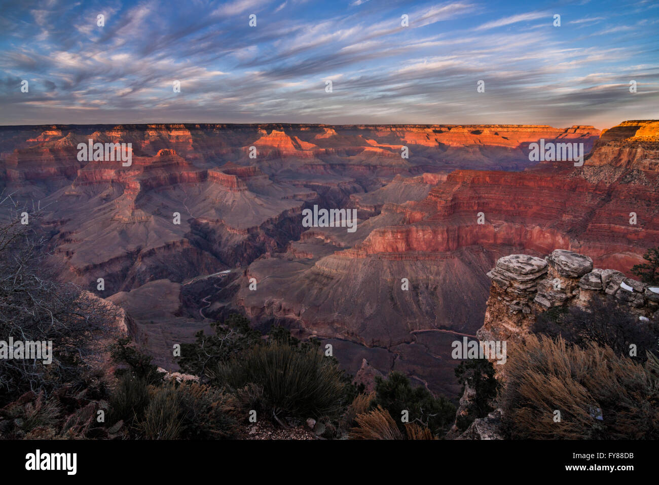 The last rays of the setting sun light up the rim of the Grand Canyon in Arizona Stock Photo