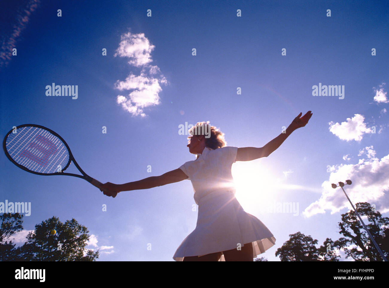Female tennis player hitting the ball with a racket - Stock Image