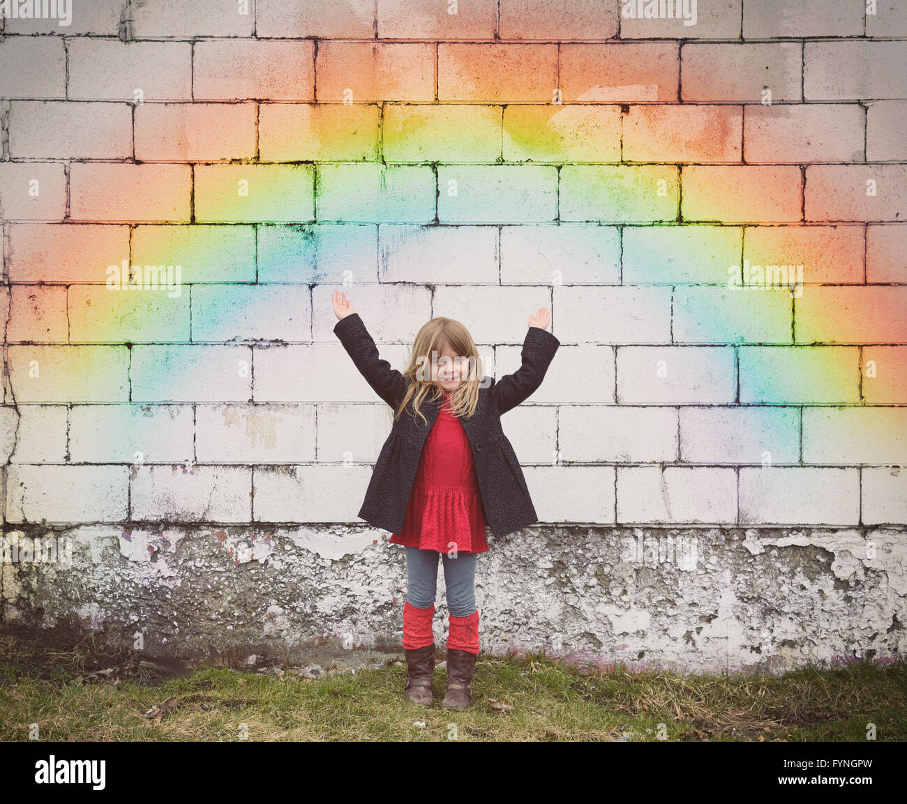 A happy little girl is standing against an old brick wall with a colorful rainbow and her hands are raised for a - Stock Image