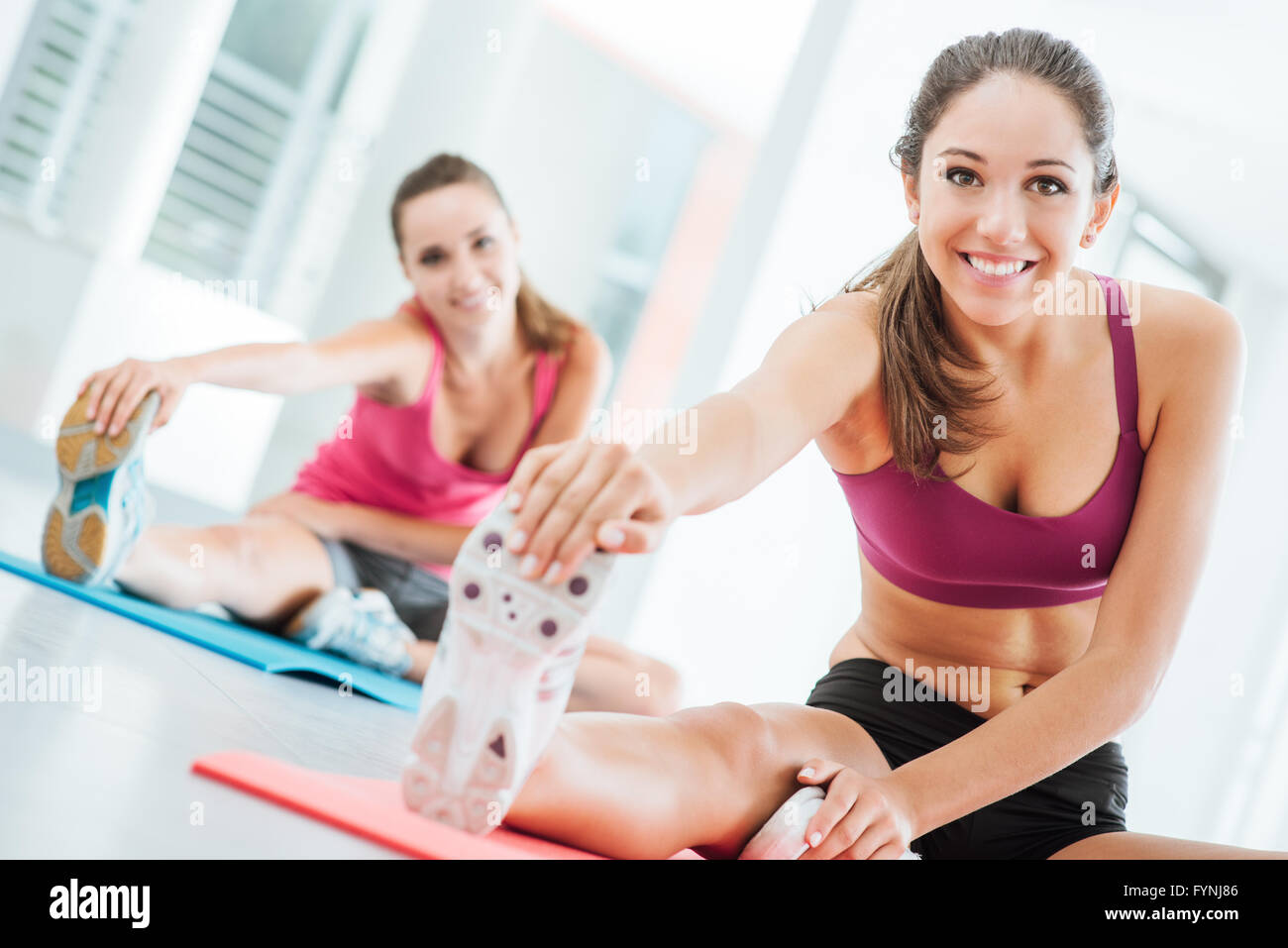 Smiling young women at the gym doing a stretching exercise for legs on a mat, fitness and health concept - Stock Image