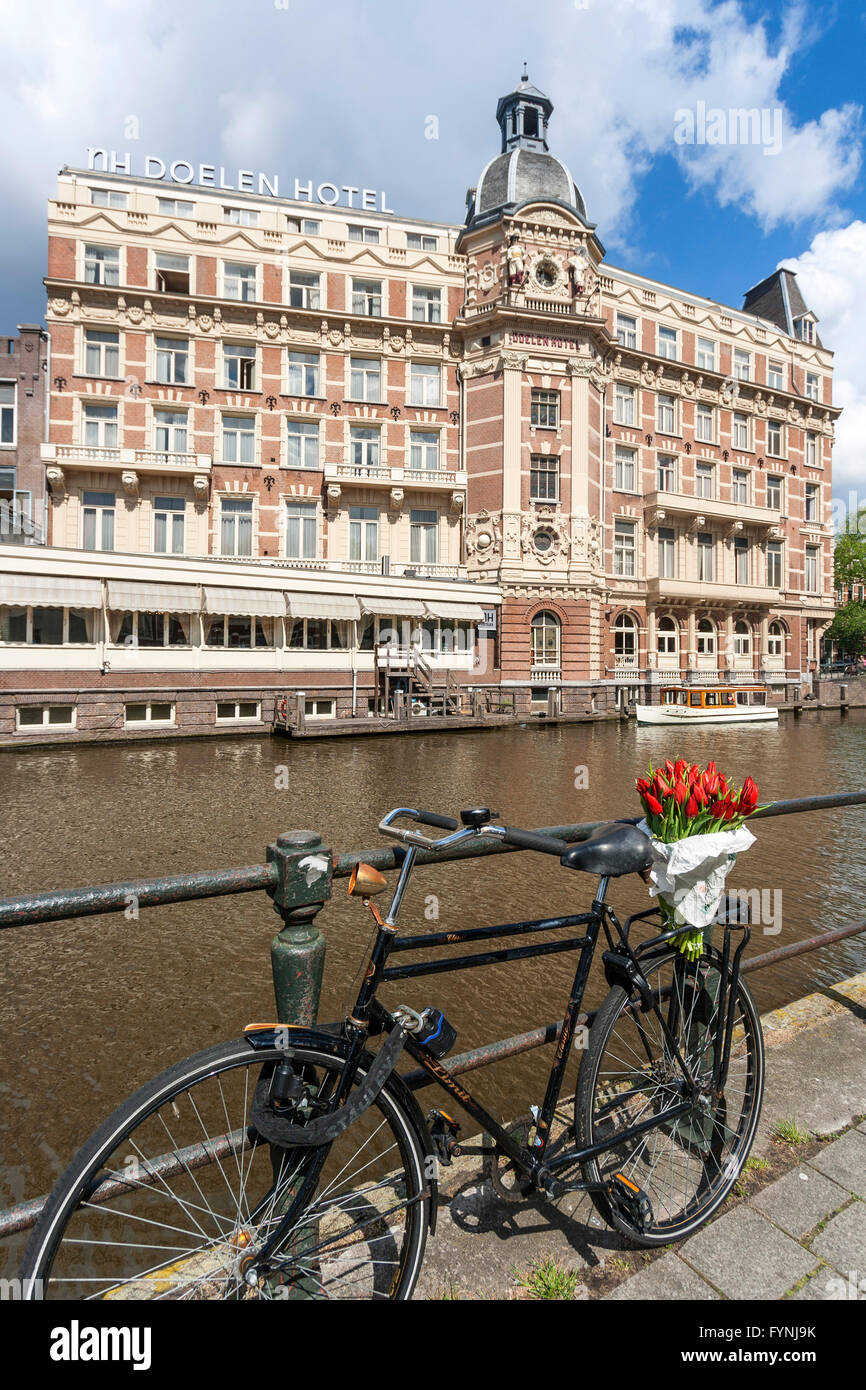 NH Doelen Hotel, bicycle with tulips, Amsterdam, Netherlands Stock Photo