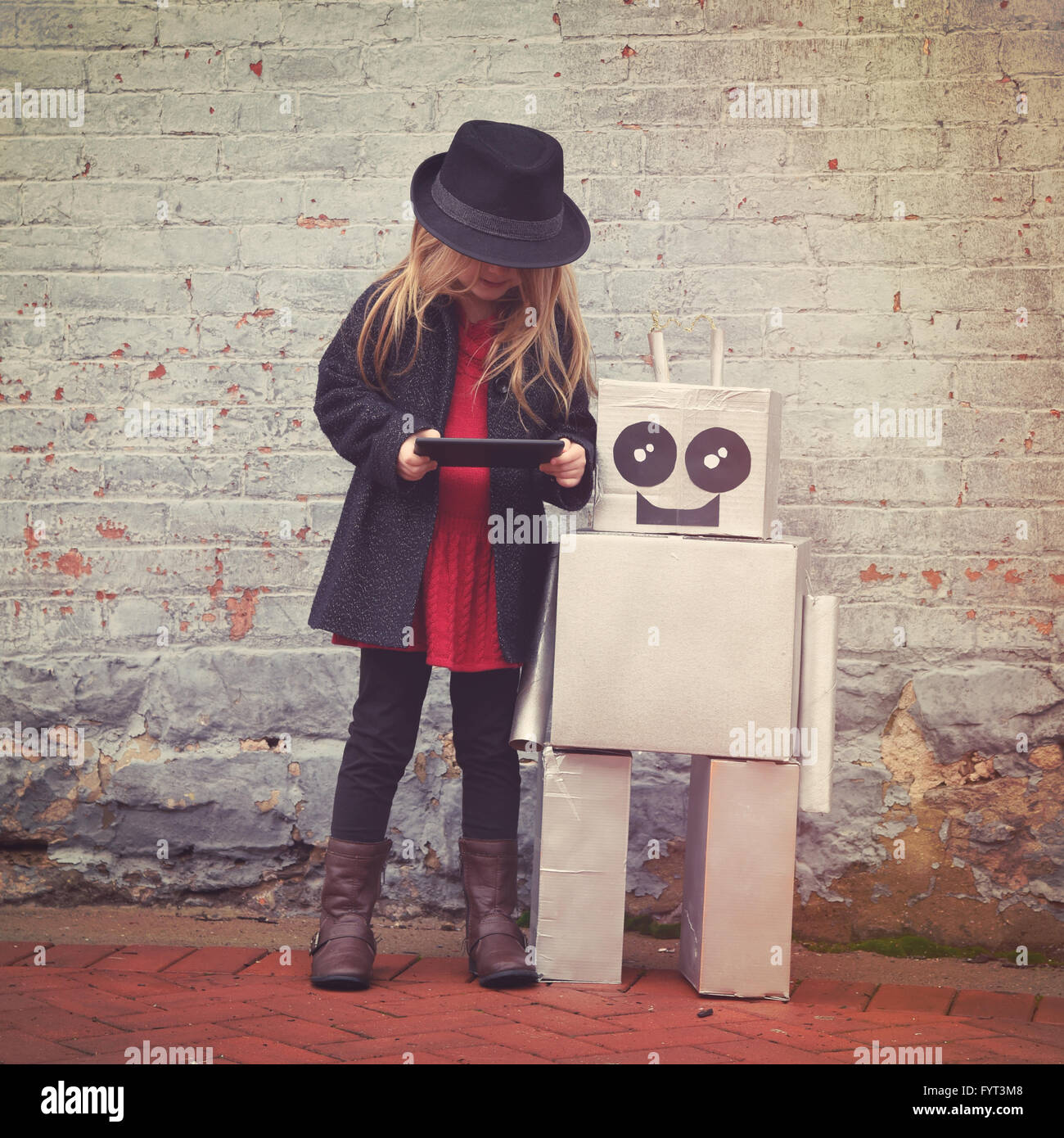 A little hipster child wearing is holding a tablet with her toy robot friend downtown for a happiness or technology - Stock Image