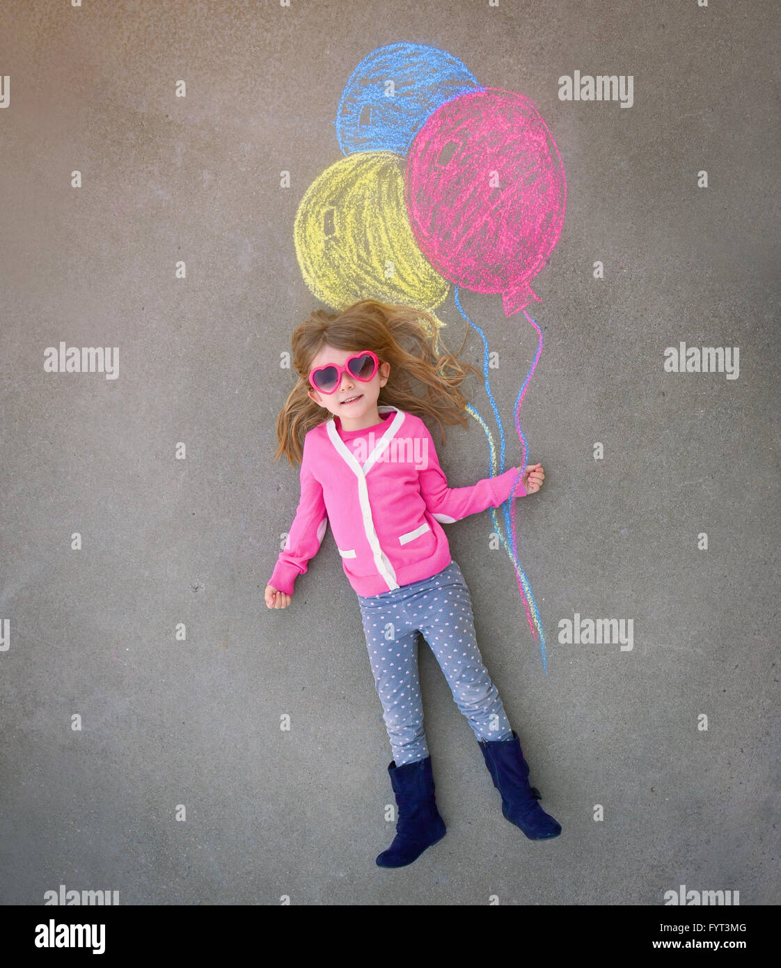 A cute little girl with sunglasses is holding creative chalk balloons drawn on the sidewalk for a imagination, summer - Stock Image