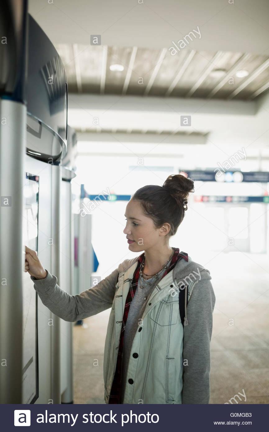 Teenage girl using ticket machine at train station - Stock Image