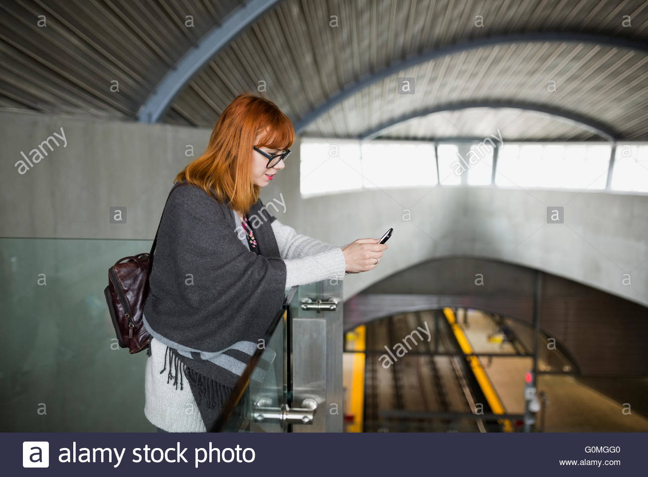 Woman texting with cell phone at train station - Stock Image