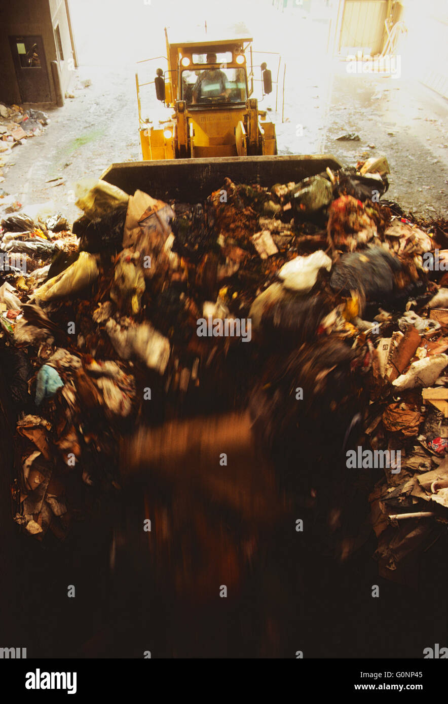 HEAVY EQUIPMENT SORTS TRASH AT A TRANSFER STATION AT CLARKSTOWN, NEW YORK, RECYCLING CENTER & LANDFILL - Stock Image