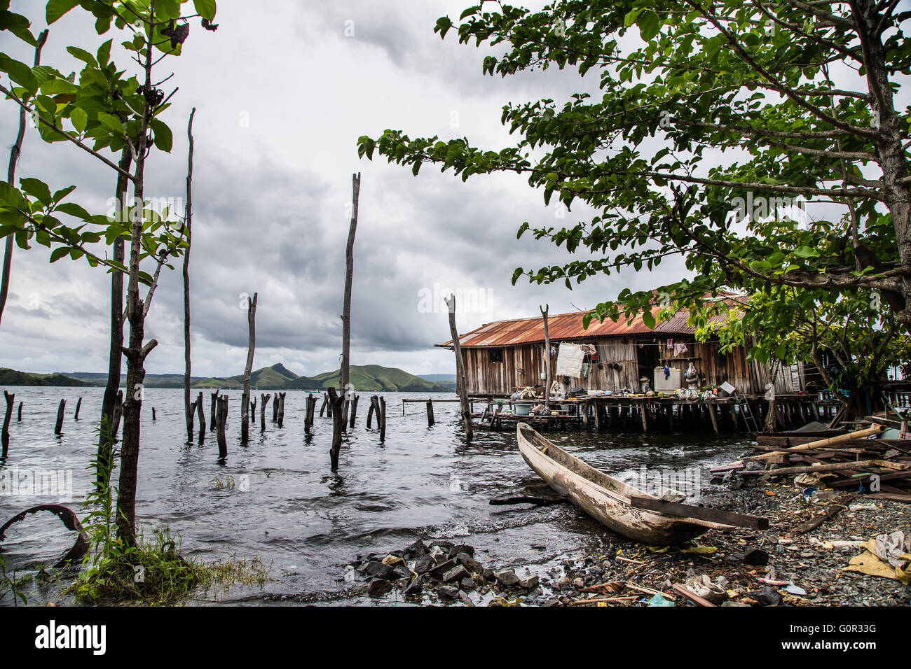 House on the sea and a boat parked near it, in Jayapura, West Papua, Indonesia - Stock Image