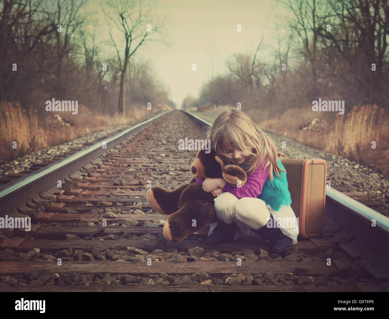 A little girl is sitting on an old train track outside and hugging a teddy bear for a vintage memory or travel concept. - Stock Image
