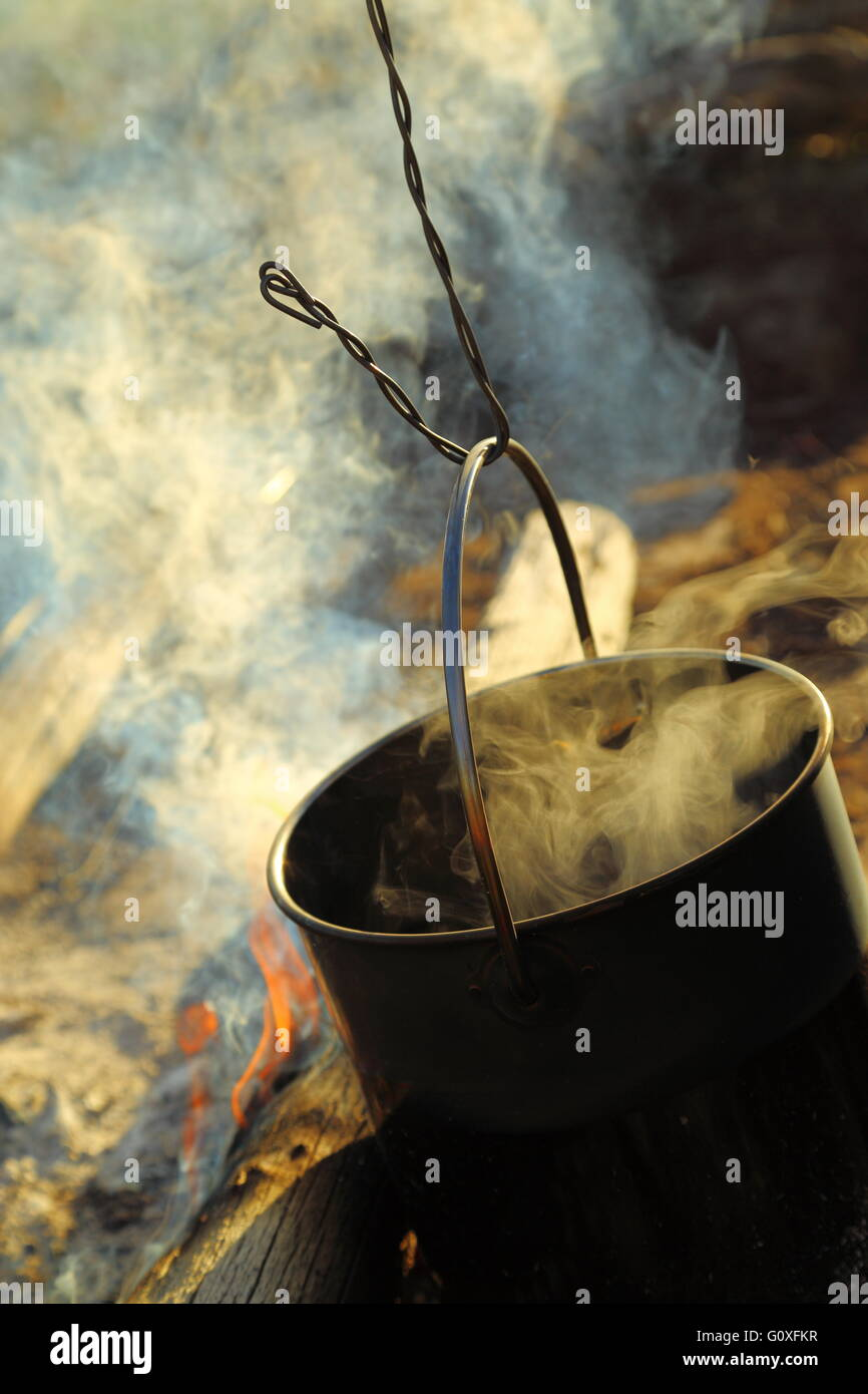 A large stainless steel cooking pot being brought to a boil in an open camp fire in Queensland, Australia. - Stock Image