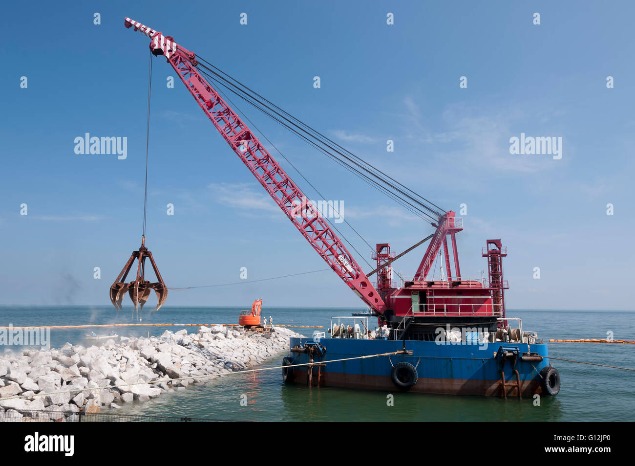Industrial floating sea crane for carrying the rocks and stones - Stock Image