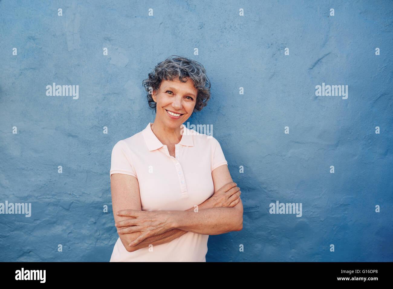 Portrait of attractive mature woman with her arms crossed standing against blue background. She is leaning to a - Stock Image