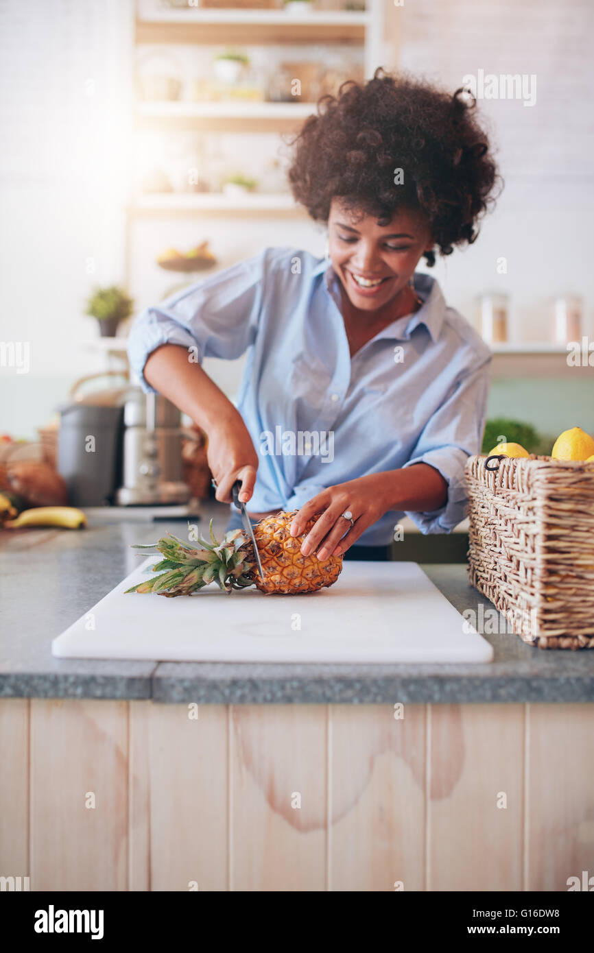 Young african woman standing behind bar counter cutting a pineapple on chopping board. Female working at juice bar - Stock Image