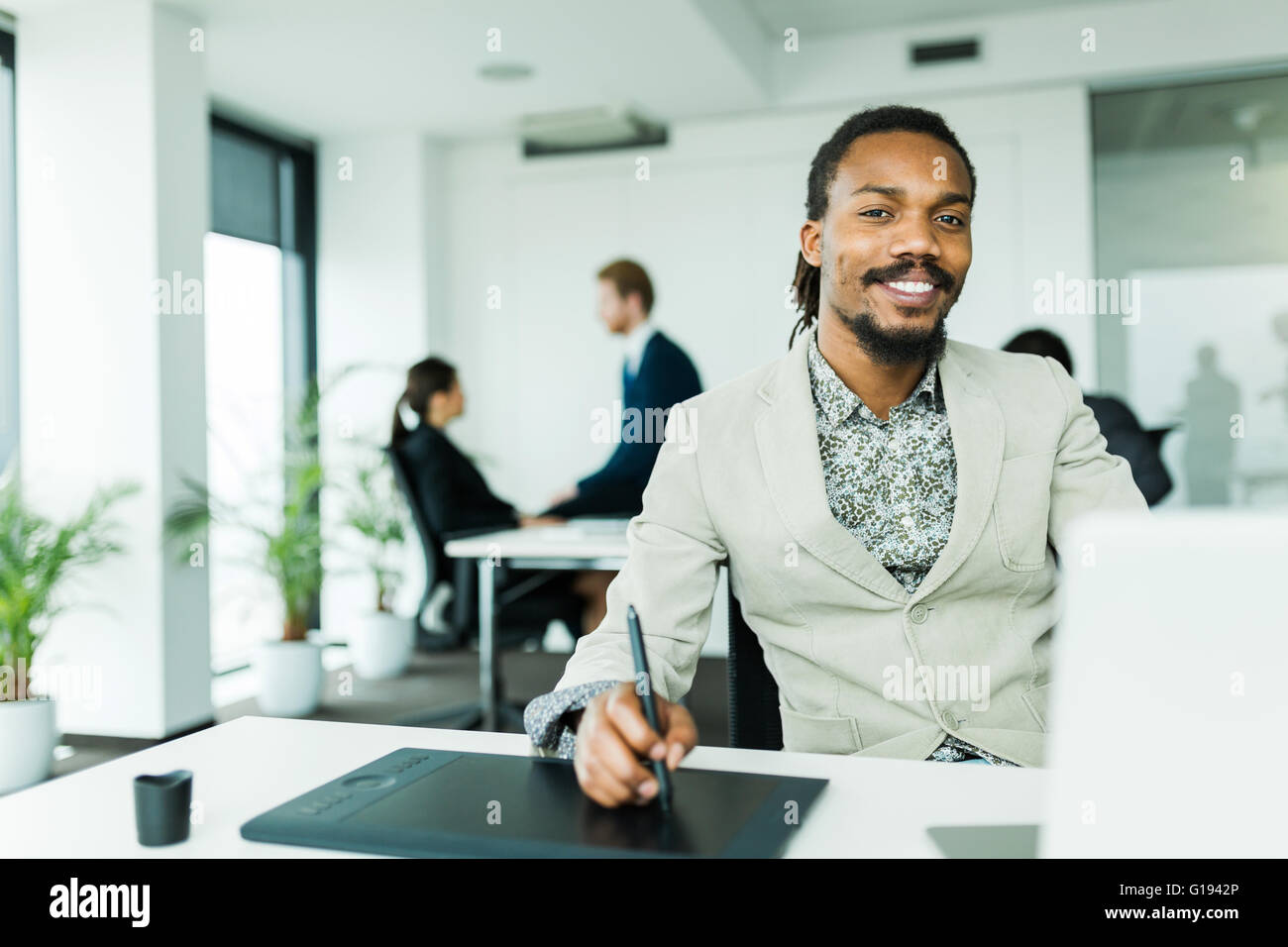 Black handsome graphics designer  with dreadlocks using digitizer in a well lit, tidy office environment  while - Stock Image