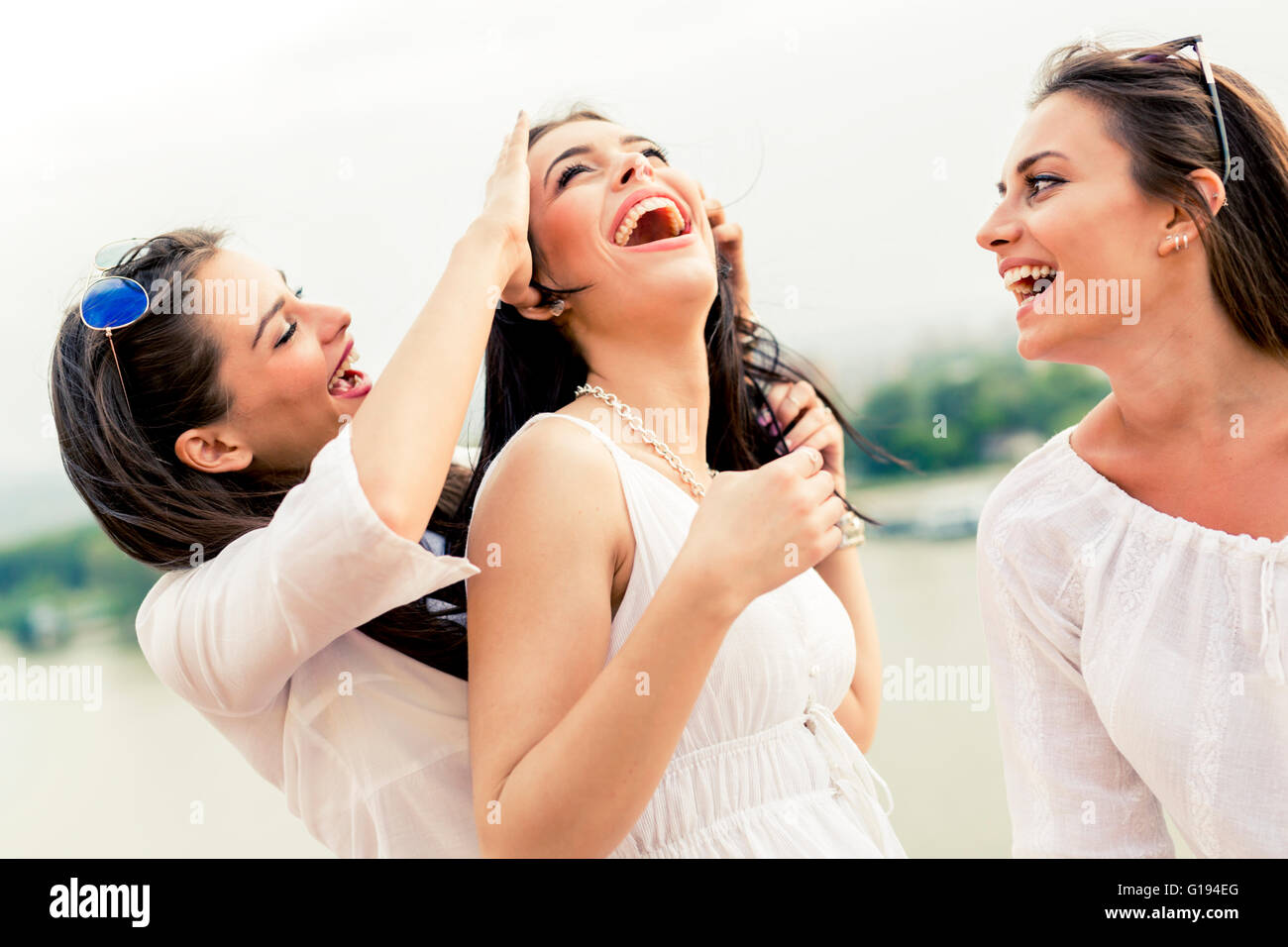 Cheerful women having fun outdoors and laughing happily - Stock Image