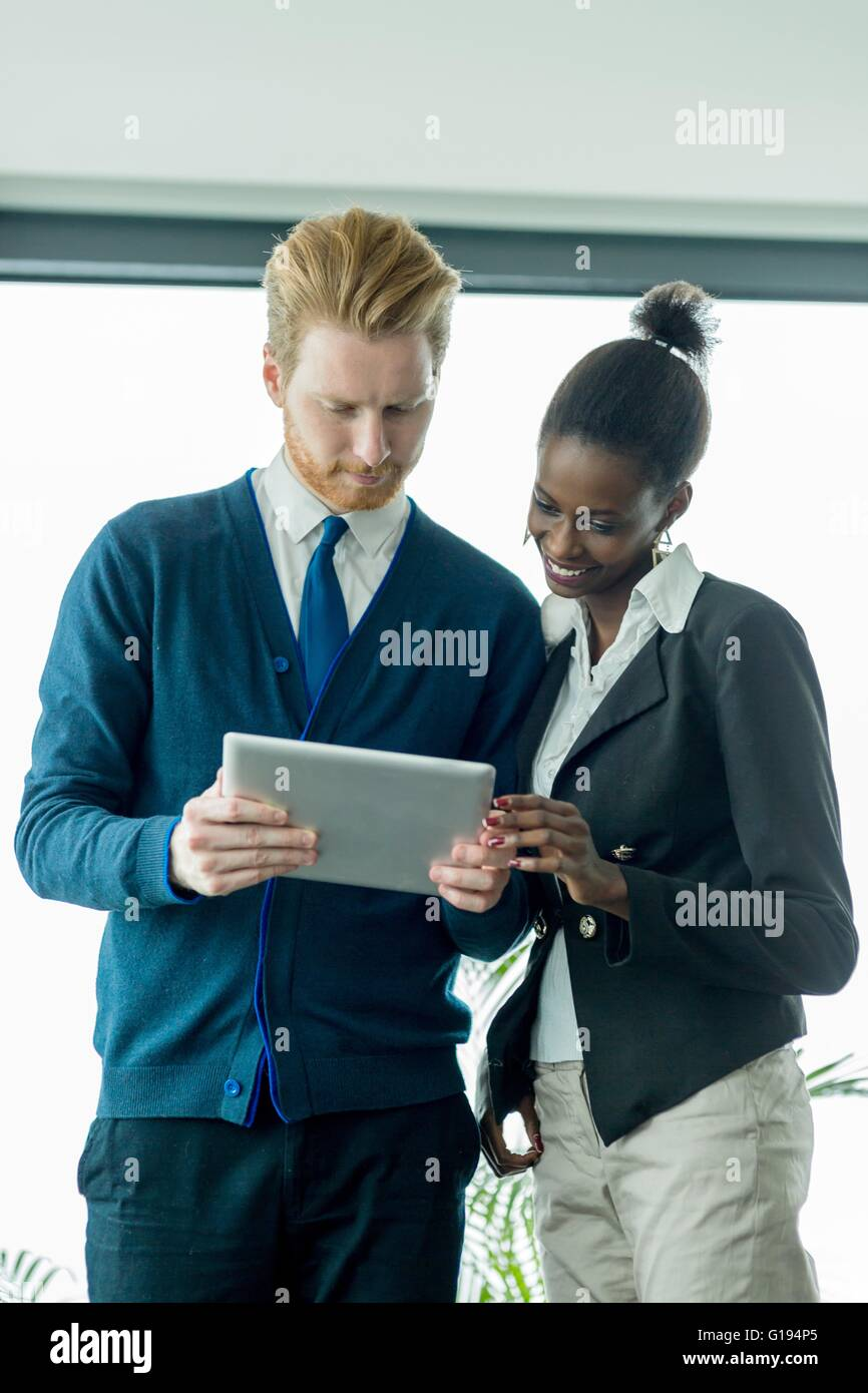 Businesspeople looking at a tablet and discussing achievements - Stock Image