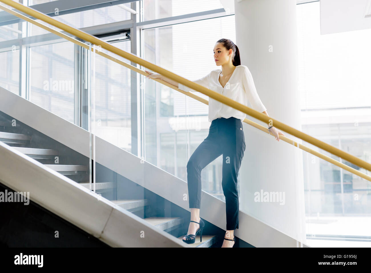 Businesswoman on stairs in a modern office Stock Photo