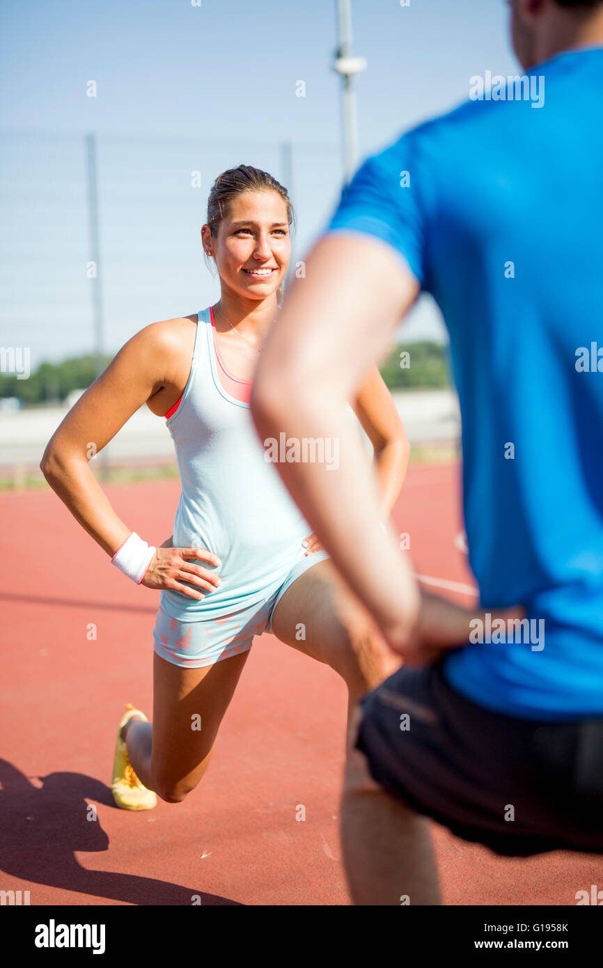 Young athletic man and woman stretching outdoors on a hot summer day facing each other - Stock Image
