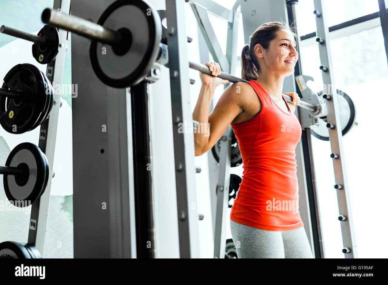 Focused young beautiful woman lifting weights in a gym - Stock Image