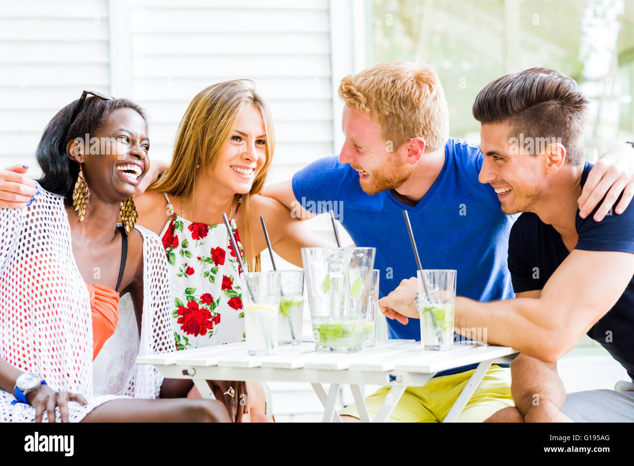 Friends laughing and hugging each outher outdoors and being happy - Stock Image