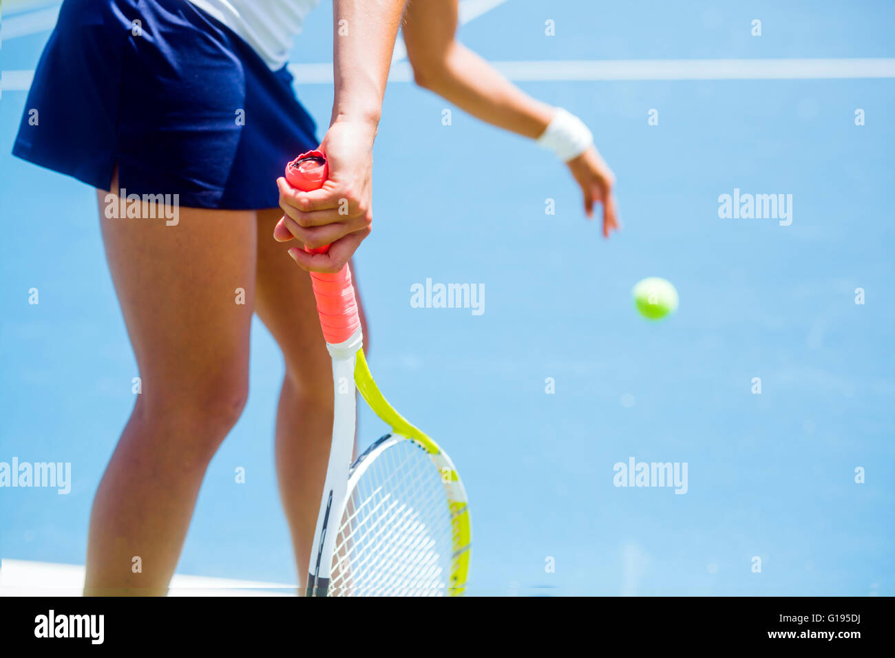 Beautiful female tennis player serving outdoor - Stock Image
