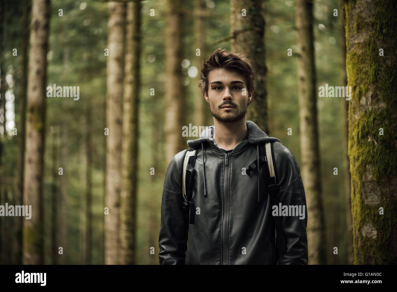 Young handsome man exploring a forest, he is looking at camera - Stock Image